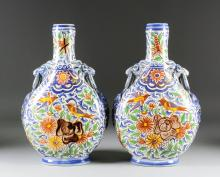 A pair of late 19th/early 20th Century Continental faience two-handled pilgrims flasks, decorated with birds and flowering plants, 12.75ins high