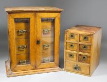 A late Victorian oak table cabinet, fitted nine small drawers enclosed by a pair of bevelled glass panelled doors, on moulded base, 16ins wide x 11ins deep x 18ins high (lacking key), and a small walnut nest of seven small drawers with recessed brass handles, 8ins wide x 10ins deep x 12ins high