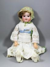 A late 19th / early 20th Century Simon and Halbig bisque headed doll, with closing eyes and open mouth showing teeth, the head with factory mark and moulded with  No. 1909, and 5 1/2,  with composition body and limbs, 24ins high, wearing a lace dress and undergarments,
