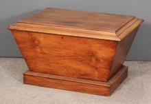 An early Victorian walnut rectangular cellaret of sarcophagus shape, the flat top enclosing lined interior on plinth base, 31ins wide x 24ins deep x 19.5ins high, (split to top end of brackets)