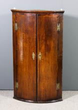 A George III oak bow front hanging corner cupboard inlaid with mahogany bandings, with moulded cornice, fitted two shelves enclosed by a pair of doors, 26ins wide x 45.25ins high, (some shrinkage to doors)