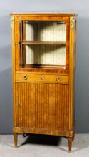 An early 20th Century French walnut, kingwood and gilt brass mounted display cabinet, with red veined marble slab to top, fitted with one shelf, enclosed by a single glazed door inlaid with bandings, central narrow frieze drawer and cupboard under, flanked by rounded front corners inlaid stylized fluted ornament and on turned feet with gilt brass sabots, 27ins wide x 15.25ins deep x 58.5ins high