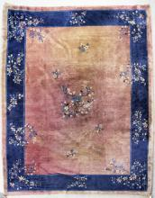 A Chinese carpet woven in navy blue, pale blue, and ivory with floral sprigs on a plain fawn ground, within conforming blue borders, 10ft 6ins x 9ft 3ins