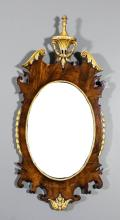 A mahogany framed and parcel gilt oval wall mirror, with bow front reeded and bellflower cresting, the frame of shaped outline with scroll carving to top, bellflower ornament to side and conforming apron, inset with plain oval mirror plate, 39ins x