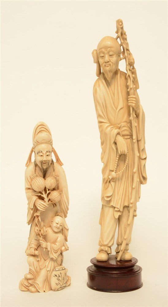 A Chinese ivory figure of a monk, on a wooden base, late Qing period, H 36
