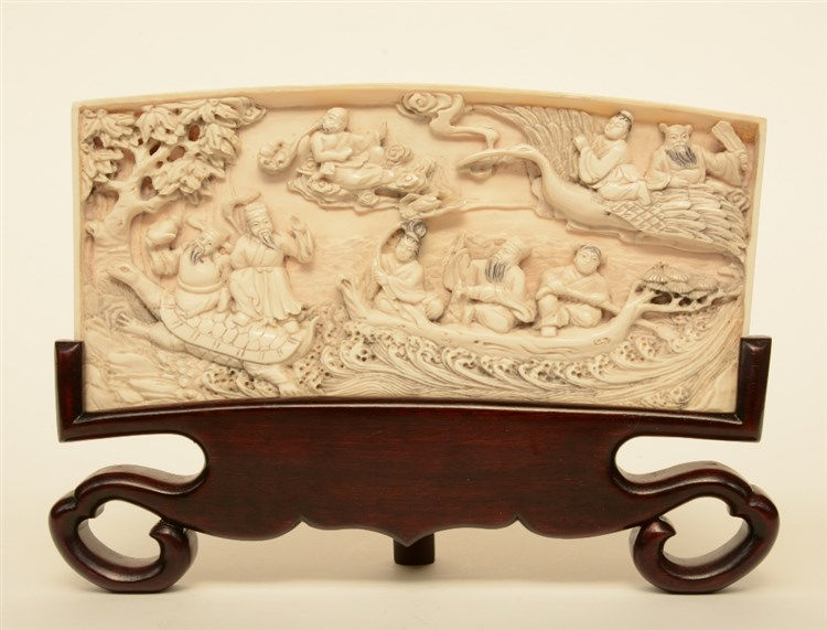 A Chinese ivory plaque on a wooden base depicting the Eight Immortals cross