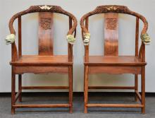 A pair of Chinese armchairs in exotic wood, the horseshoe-shaped back richl