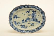 A Chinese oval dish with profiled rim, blue and white decorated with a land