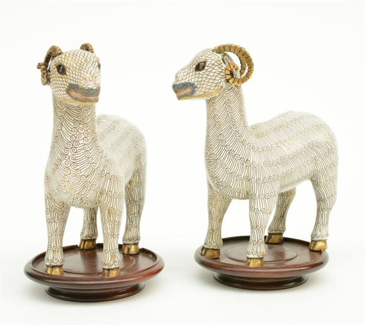 A pair of Chinese cloisonné figures depicting goats, on a wooden base, 19th