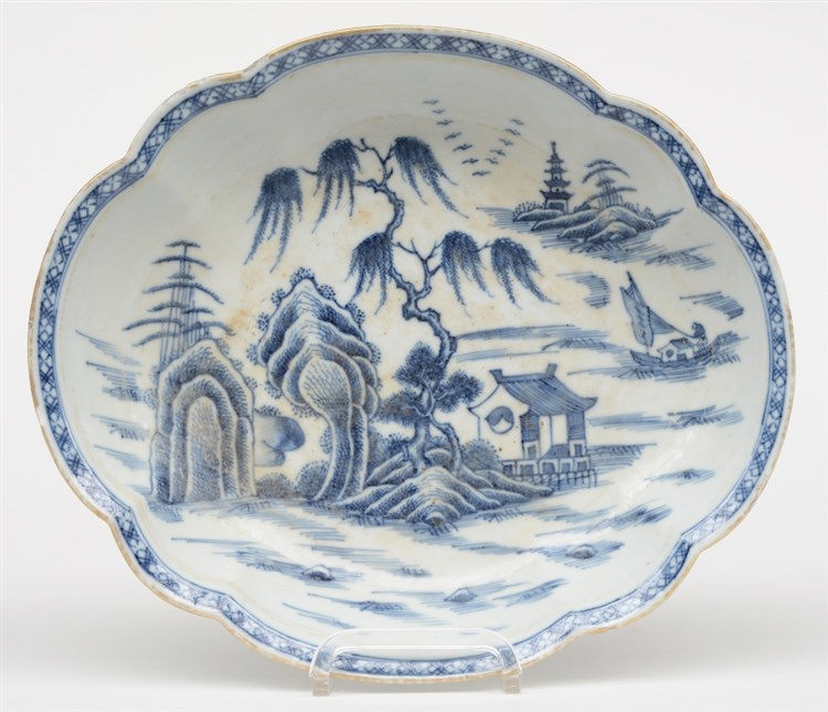 A Chinese oval dish with a profiled rim, blue and white decorated with a la