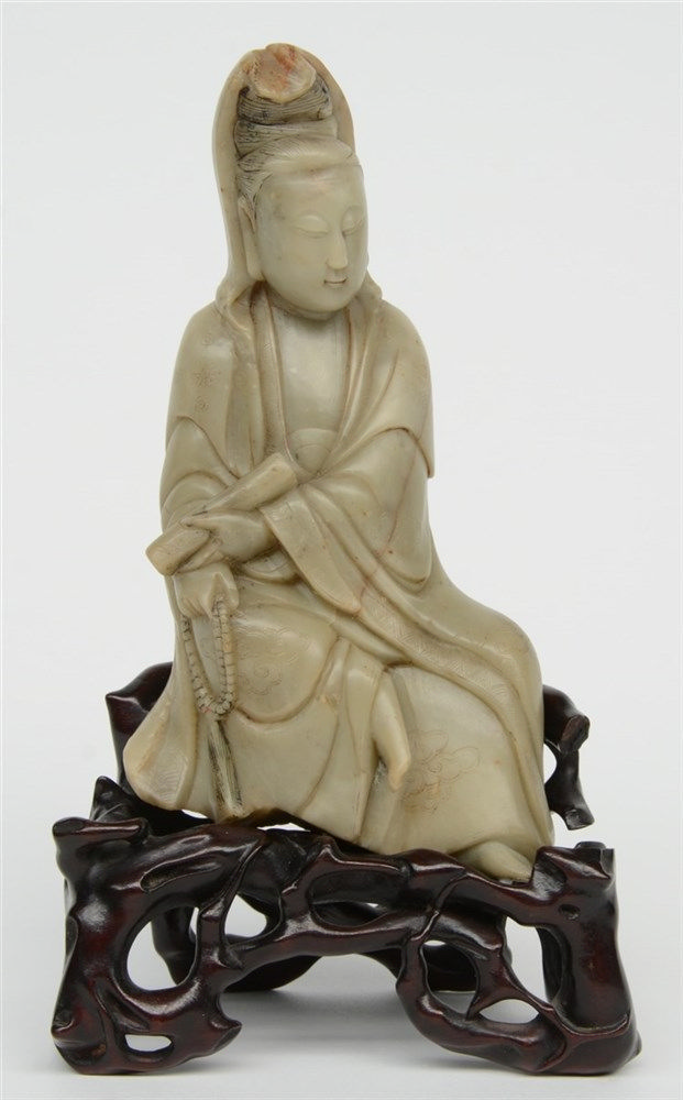 A Chinese steatite sculpture representing a Guanyin, on a wooden base, 18th