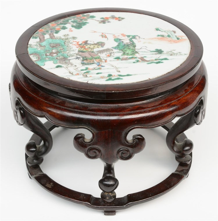 A Chinese wooden stool with a famille verte plaque decorated with a genre s