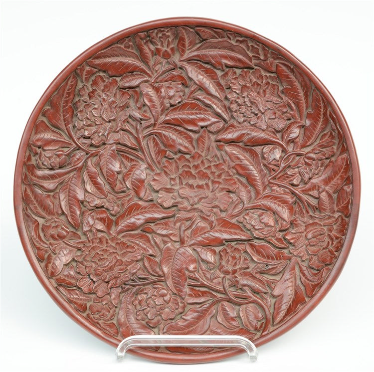 A red Peking lacquered plate with relief decorations, marked, Diameter 35 c