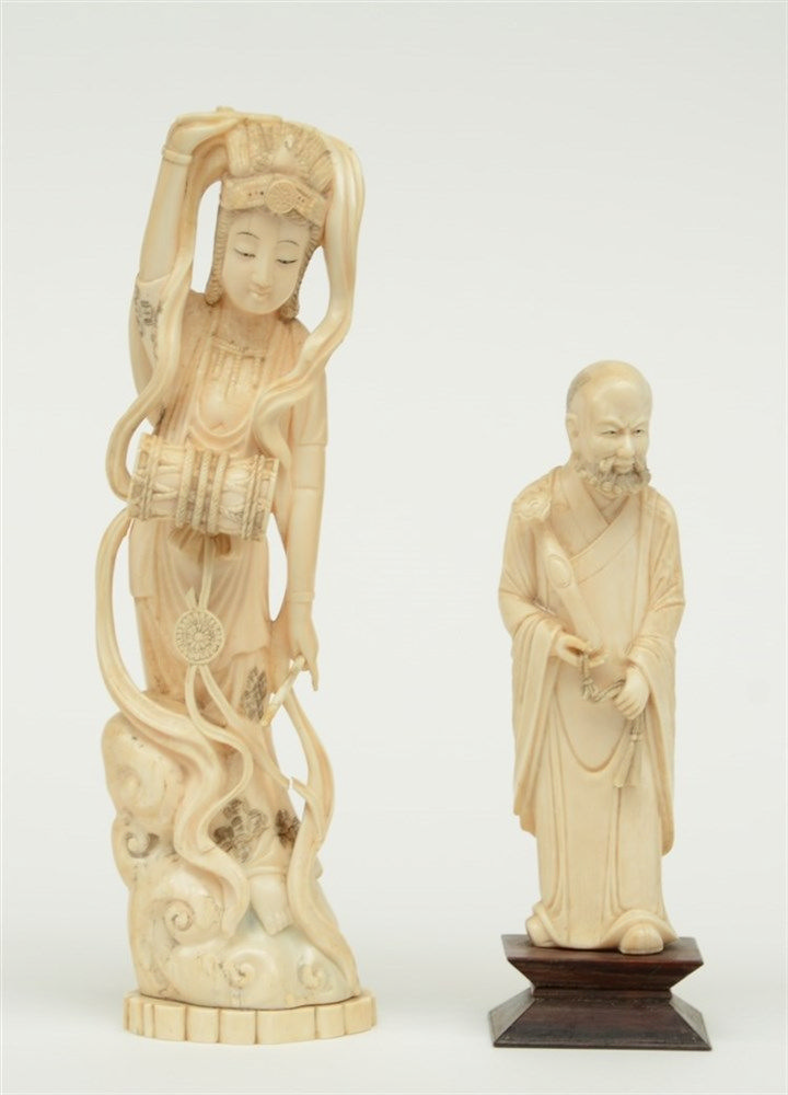 A Chinese ivory sage bearing a ruyi scepter, discrete scrimshaw decoration,