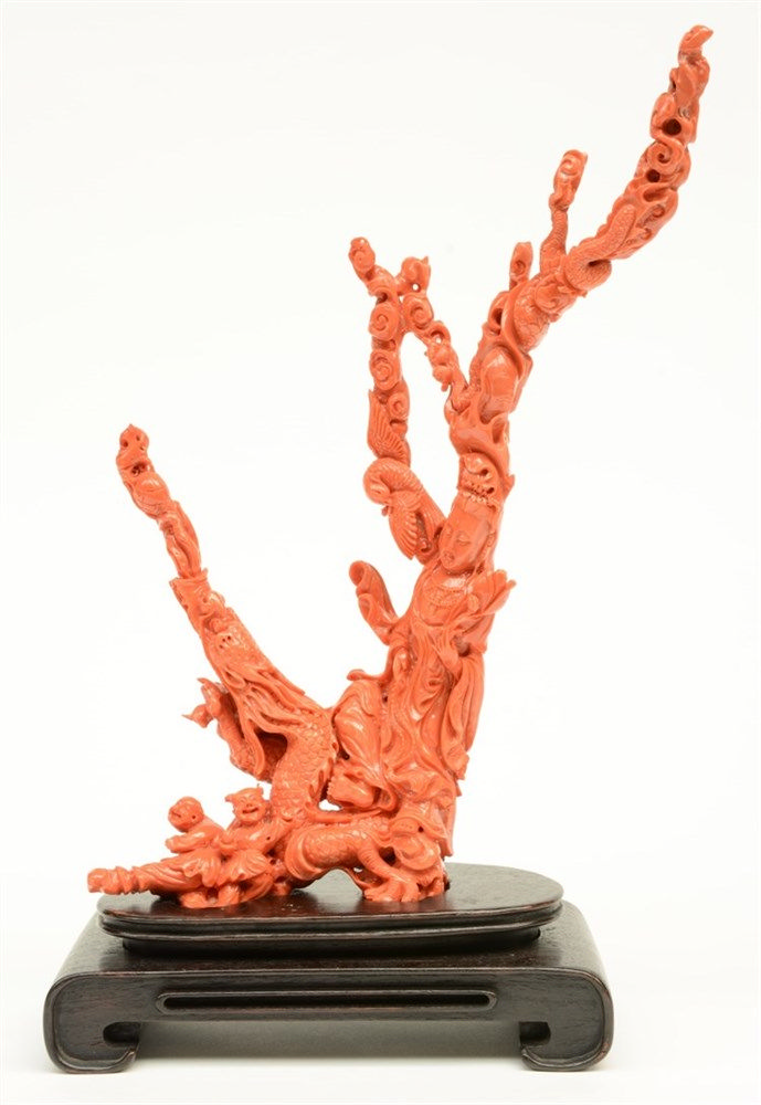 A Chinese red coral sculpture depicting a Guanyin sitting on a red dragon a