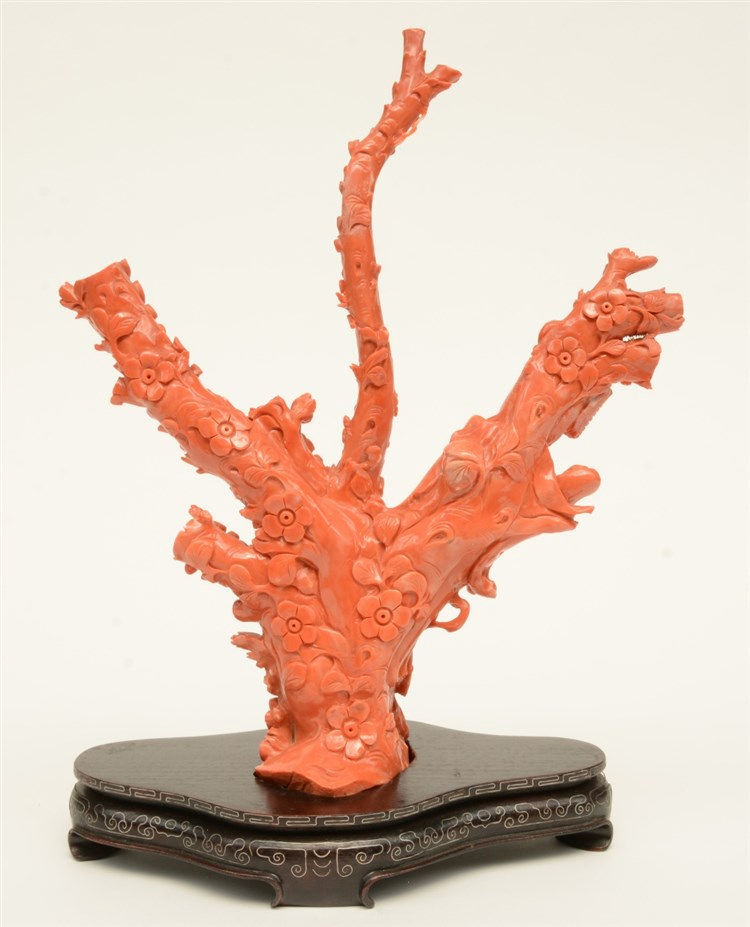 A Chinese red coral sculpture depicting a Guanyin in a garden, late Qing dy