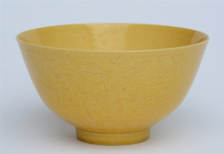 A Chinese yellow ground and relief bowl, moulded with phoenix and dragons,