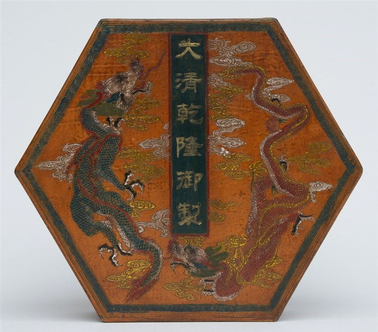 A Chinese octagonal wooden box and cover, painted with dragons and other sy