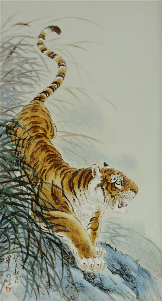 A Chinese polychrome plaque in a wooden frame, decorated with a tiger in a
