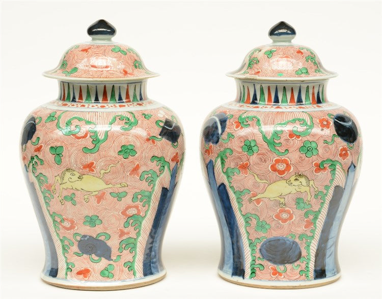 A pair of Chinese wucai vases and covers, decorated with horses, blue rocks