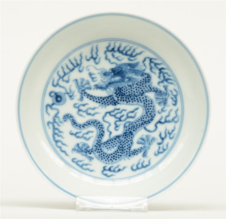 A Chinese blue and white plate decorated with dragons and flaming pearls, m