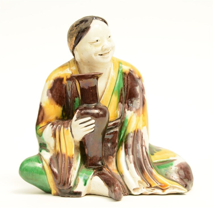 A Chinese Sansai sculpture depicting a seated figure holding a vase, Kangxi