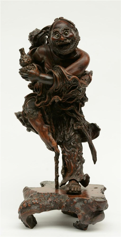 A Chinese walnut carved sculpture depicting a mythical figure, 19thC, H 64