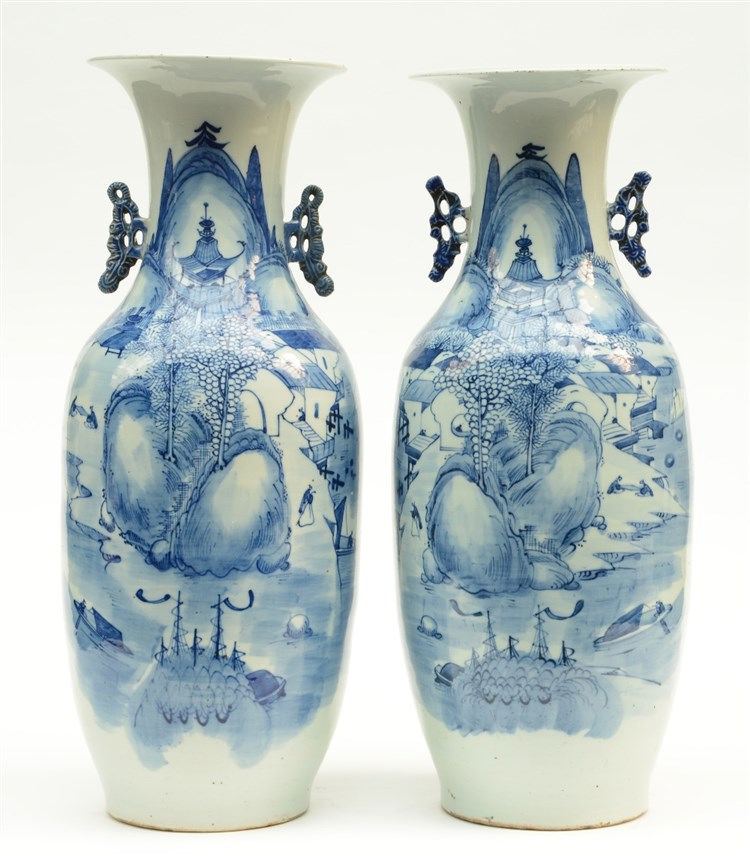 A pair of Chinese blue and white vases, decorated with figures in a mountan