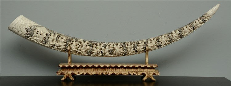 An impressive Chinese ivory tusk, richly carved with an animated scene, on