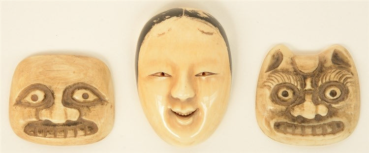 Three early Meiji period Japanese ivory netsuke in the form of masks, one o