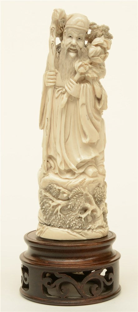 A Chinese ivory sculpture depicting a sage accompanied by a young girl, scr