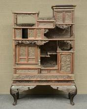 A Japanese wooden display cabinet, carved with birds, flowerbranches and a