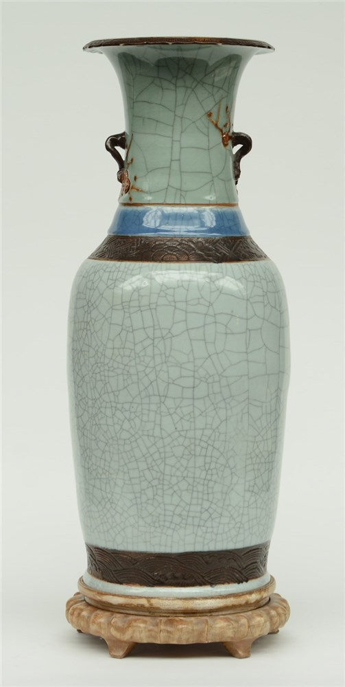 A Chinese stone- crackleware vase, relief decorated, on a matching wooden b