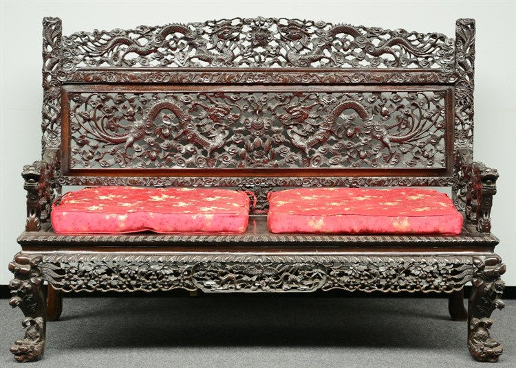 A Chinese richly hardwooden carved settee, representing dragons, bats and o