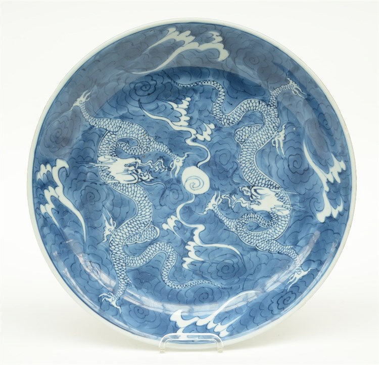 A Chinese blue and white plate decorated with dragons and the flaming pearl