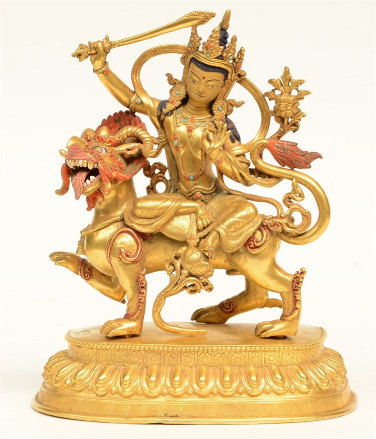 A fine Tibetan gilt bronze Boddhisatva seated on a mythical animal, polychr