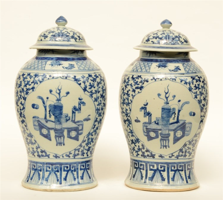 A pair of 19thC Chinese blue and white vases and covers, painted with flora