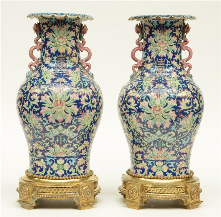 A pair of Chinese polychrome vases, relief moulded with dragons, symbols an