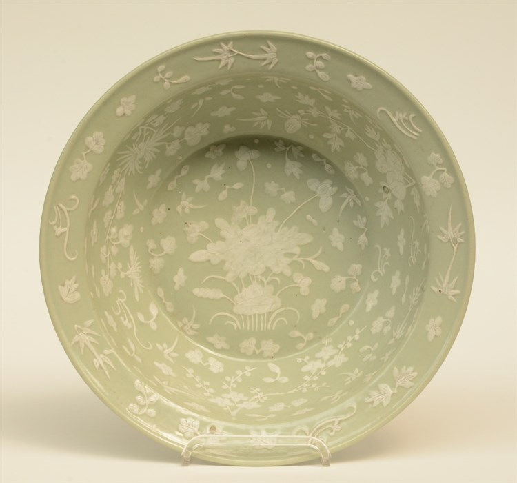 A Chinese celadon ground bowl, relief moulded with floral motifs, 19thC, H