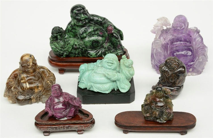 Seven Chinese laughing Buddai, in various semi-precious stones, some on a w