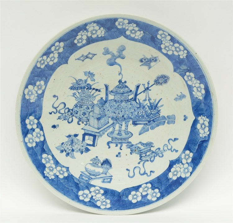 A Chinese blue and white plate decorated with antiquities and prunus blosso