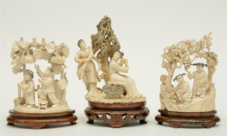 A Chinese ivory sculpture figuring two maiden, scrimshaw decorated, on a wo