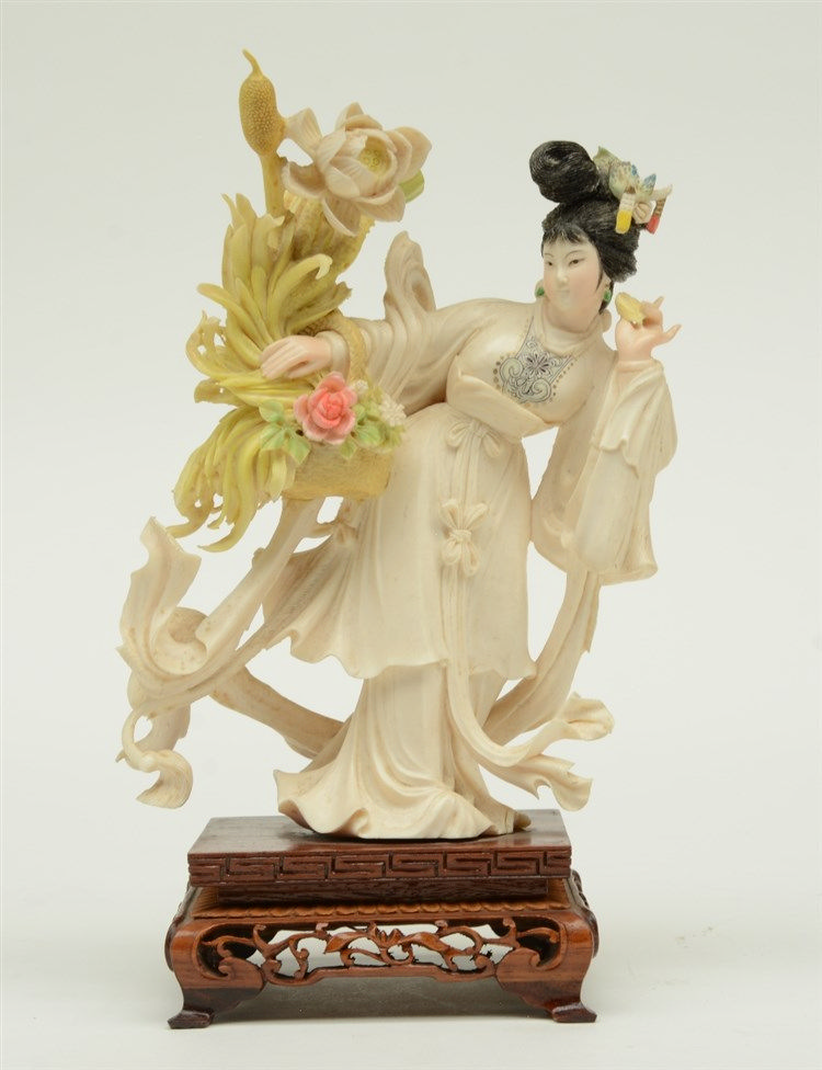 A Chinese ivory sculpture, polychrome decorated, depicting a court lady hol