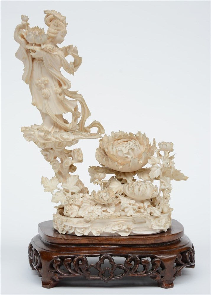 A Chinese ivory sculpture depicting an Immortal on a cloud surrounded by fl