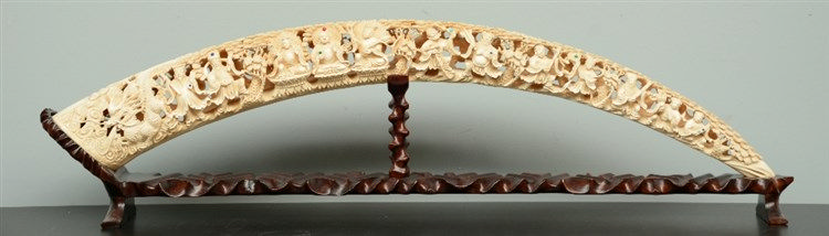 A Chinese ivory tusk, carved with the Eight Immortals, inlaid with various