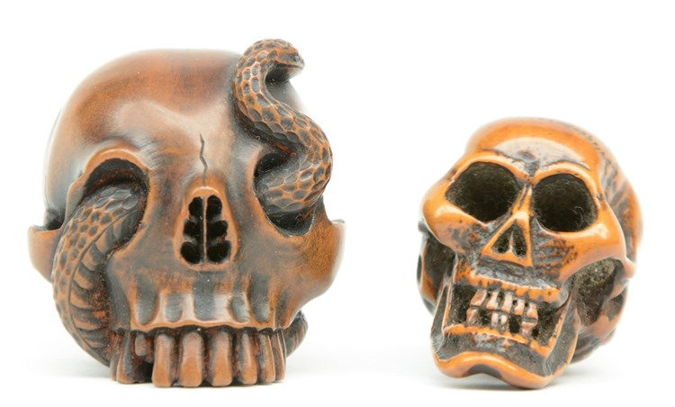 Two Japanese boxwood katabori netsuke in the form of a human skull (one wit