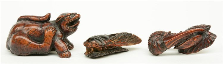 Two Japanese wooden katabori netsuke, one depicting a mythical monster and