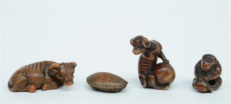 Three Japanese wooden katabori netsuke, one depicting a buffalo at rest, on