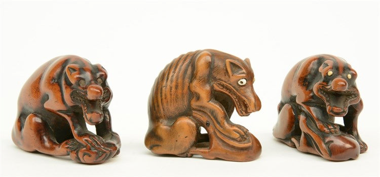 Three Japanese wooden katabori netsuke depicting wolves defending their pre