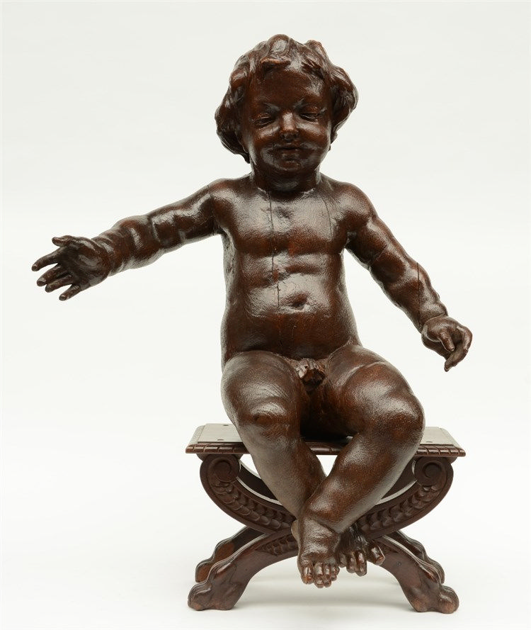 A late 17thC sculpted oak putto, mounted on a walnut bench (later date), H